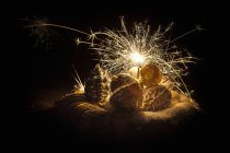 Closeup view of antique Christmas decorations and a sparkler — Stock Photo