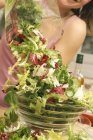 Woman strewing mixed salad — Stock Photo