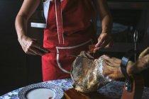 Cropped view of woman slicing Serrano ham — Stock Photo