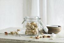 Arachidi in e accanto a un vaso di vetro su un tavolo di cucina rustica — Foto stock