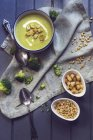Creamy broccoli soup with pine kernels and croutons over towel — Stock Photo
