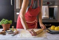 Closeup cropped view of woman rolling dough — Stock Photo