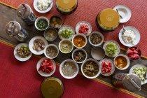 Draufsicht der verschiedenen Thai-Gerichte in Schüsseln auf roten Teppichen und Holzboden — Stockfoto
