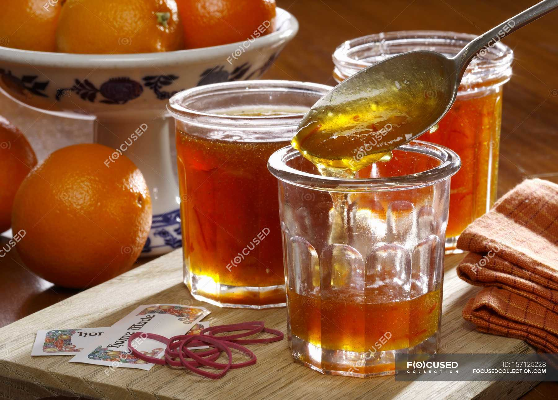Closeup view of homemade marmalade in jars with whole oranges on the background — Stock photos