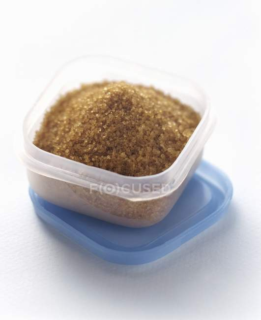 Closeup view of brown sugar crystals in plastic storage container — Stock Photo