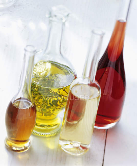 Elevated view of assorted types of herbal oil and vinegar in glass bottles — Stock Photo