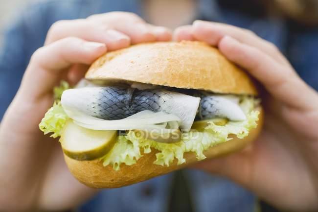 Крупним планом вид на руки, що тримає рулон риби з овочами — стокове фото