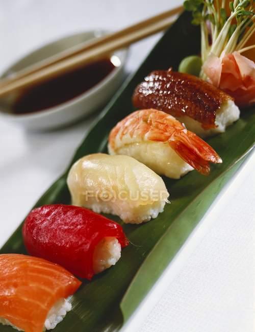 Assorted nigiri sushi on banana leaf — Stock Photo