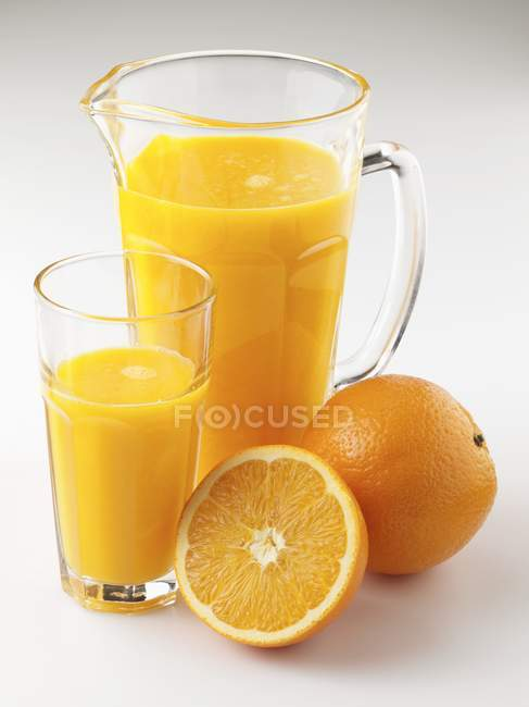 Orange juice in jug and glass — Stock Photo