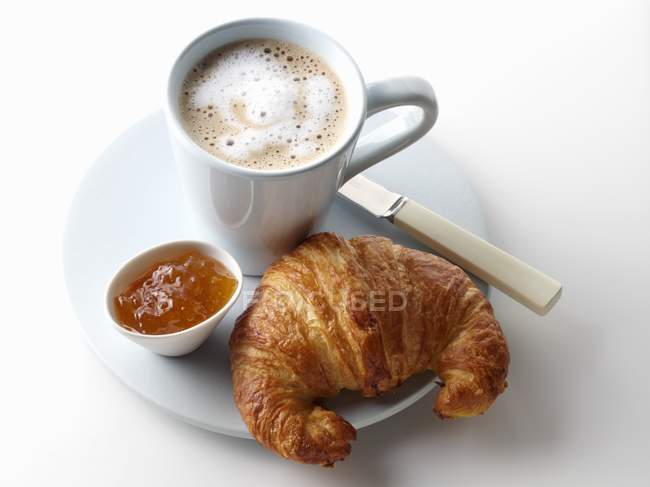 Croissant with marmalade and  cup — Stock Photo