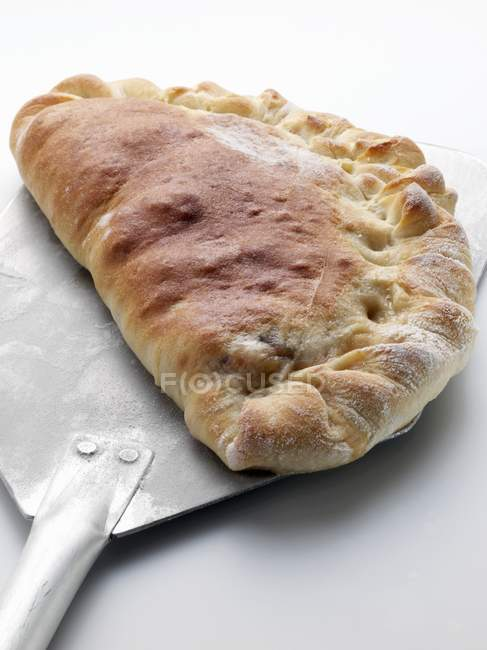 Calzone on pizza peel — Stock Photo