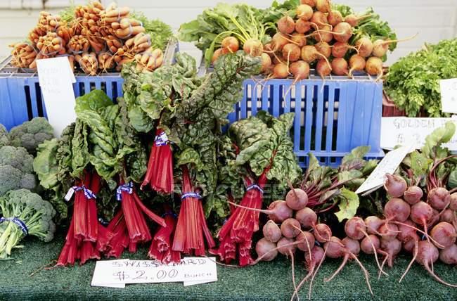 Verduras frescas en puesto en el mercado - foto de stock