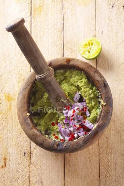 Guacamole con cebolla en un mortero sobre una superficie de madera - foto de stock