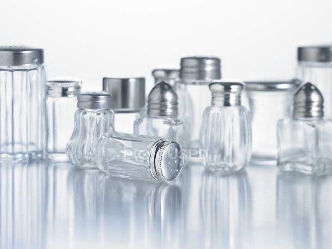 Closeup view of various salt shakers on white surface — Stock Photo