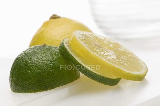 Скибочками лимона і нарізаний вапно — стокове фото