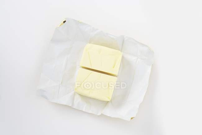 Top view of a halved pat of butter on paper — Stock Photo