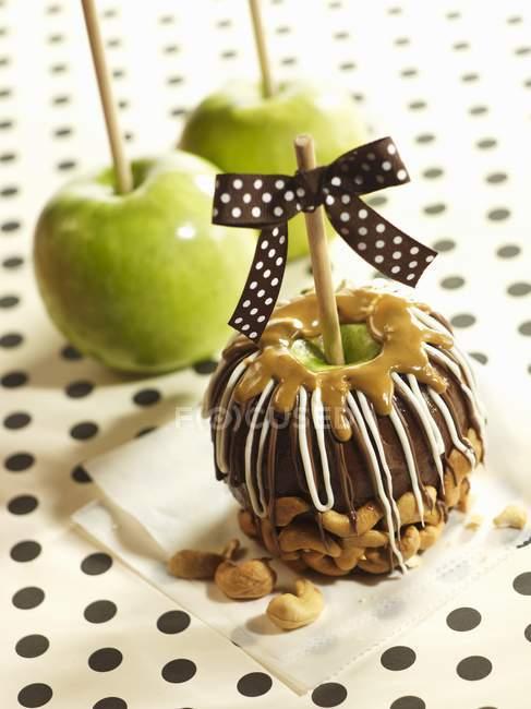 Vista de primer plano de la manzana cubierta de caramelo y chocolate con anacardos y manzanas - foto de stock