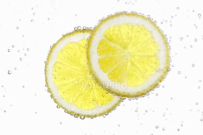 Zwei Zitronenscheiben in Wasser — Stockfoto