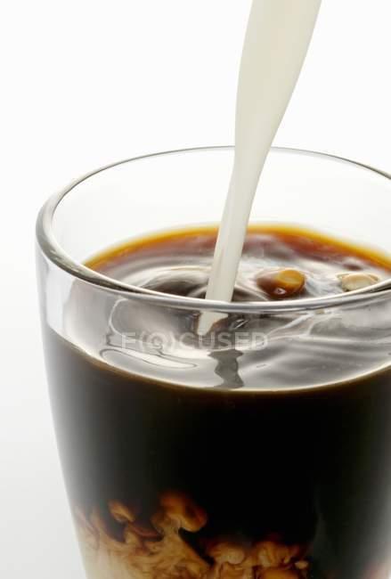 Cream poured into coffee — Stock Photo