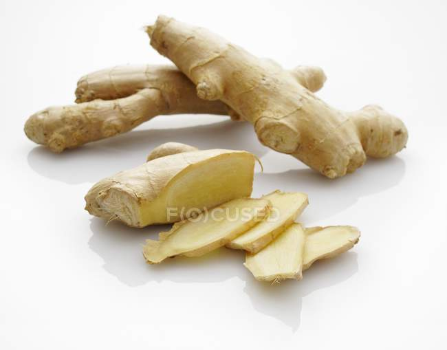 Fresh ginger roots with slices — Stock Photo