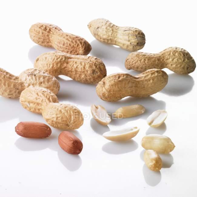 Geschälte und ungeschälte Erdnüsse — Stockfoto