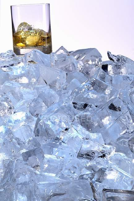 Whiskey glass on a mountain of ice cubes — Stock Photo