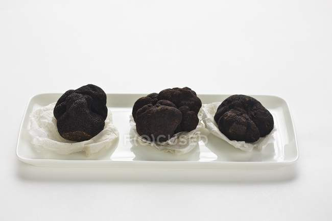Three Perigord truffles on paper — Stock Photo
