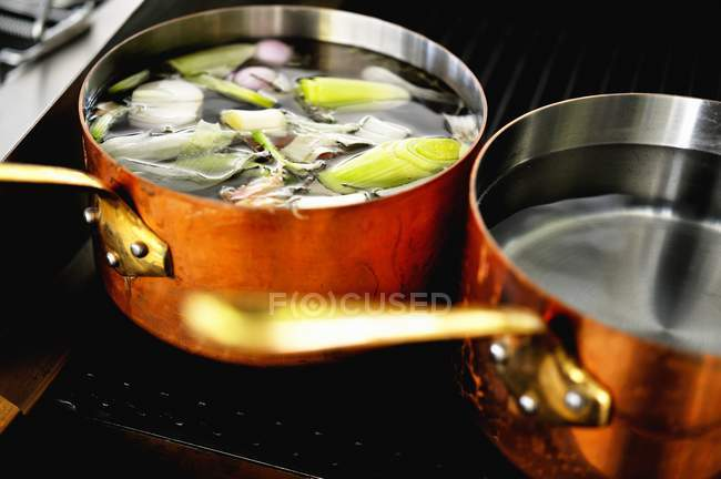 Copper pots of soup and water on a hob — Stock Photo