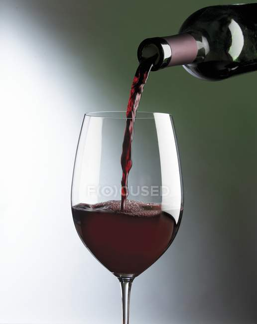 Verter en un vaso de vino tinto - foto de stock