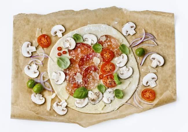 Materia prima pizza con salami y champiñones - foto de stock