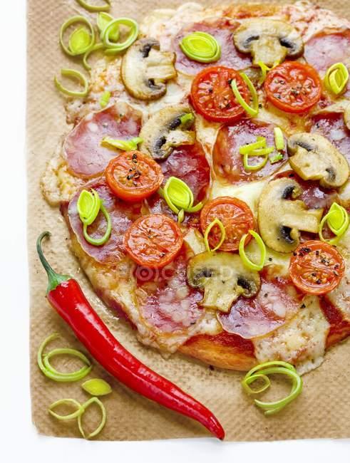 Pizza con salami, champiñones, tomates - foto de stock