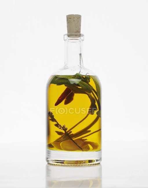 Uma garrafa de óleo de ervas com alho e pimenta — Fotografia de Stock