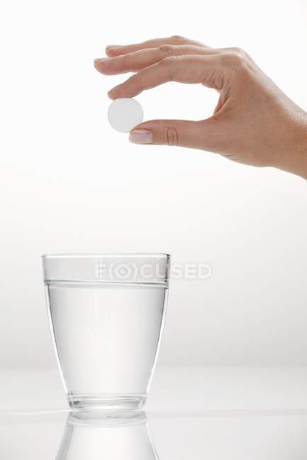 A hand holding an effervescent tablet over a glass of water — Stock Photo