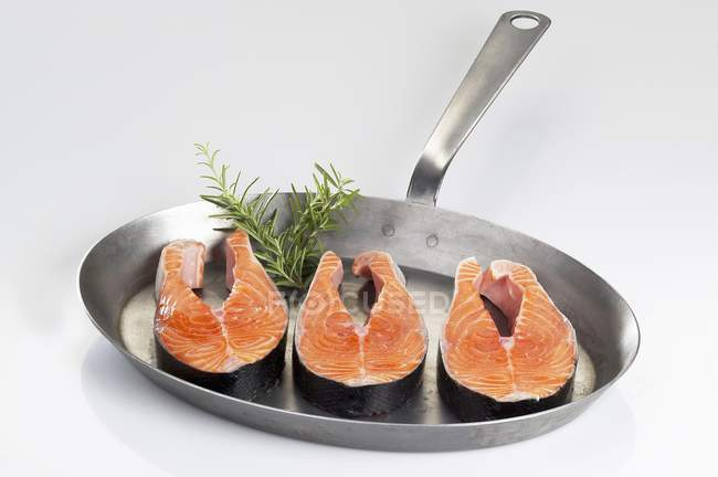 Fresh salmon steaks in frying pan — Stock Photo