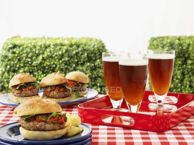 Vista de cerca de hamburguesas y cerveza en una mesa de picnic - foto de stock
