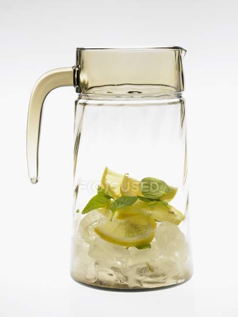 Glass carafe with lemons and ice cubes — Stock Photo