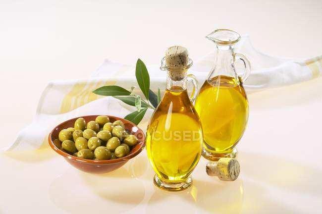 Huile d'olive en bouteilles et olives vertes — Photo de stock