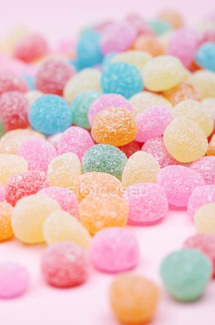 Closeup view of gum balls in sugar on pink surface — Stock Photo