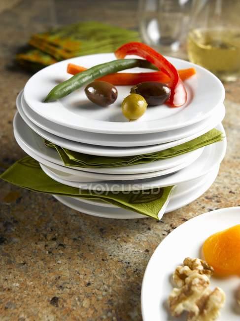 Pile di piatti bianchi alcuni con noci, verdure, olive e Healthy Munchies — Foto stock