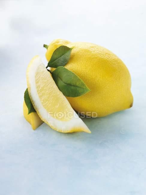 Limón con rodajas y hojas - foto de stock