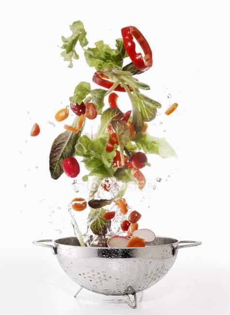 Ingredientes de ensalada que se lavan en un colador - foto de stock