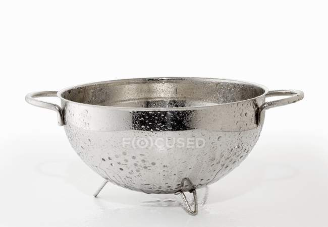 Closeup view of a wet dripping colander on white surface — Stock Photo