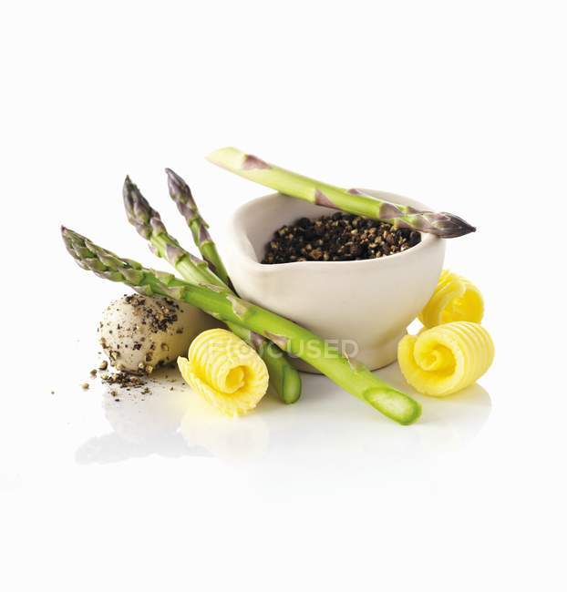 Asparagus, butter curls and peppercorns in a mortar — Stock Photo