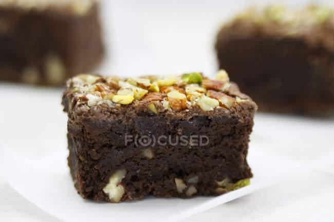 Brownie che serve con noci e pistacchi — Foto stock