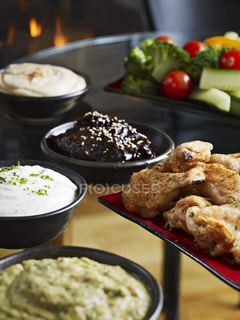 Closeup view of chicken wings with various dips — Stock Photo