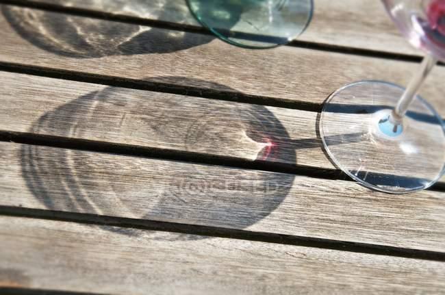 Vue rapprochée des ombres des verres à vin sur une surface en bois — Photo de stock