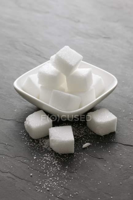 Closeup vista de cubos de açúcar em uma tigela e sobre uma superfície de xisto — Fotografia de Stock