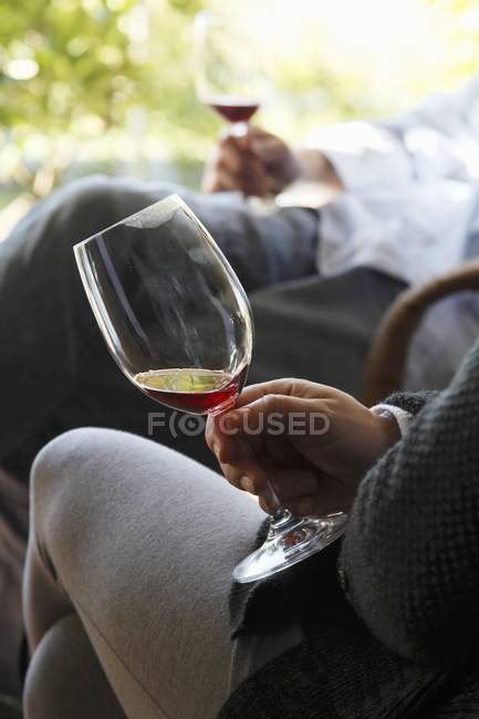Daytime cropped view of two sitting men holding glasses of wine — Stock Photo