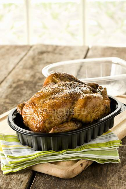 Whole roasted Chicken in Plastic Container — Stock Photo