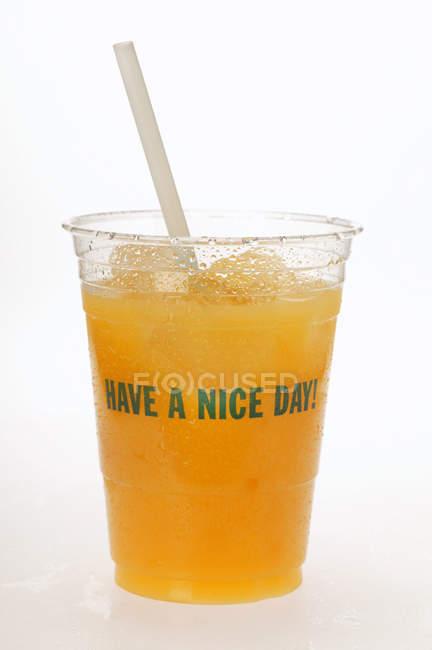 Jugo de naranja en vaso plástico - foto de stock